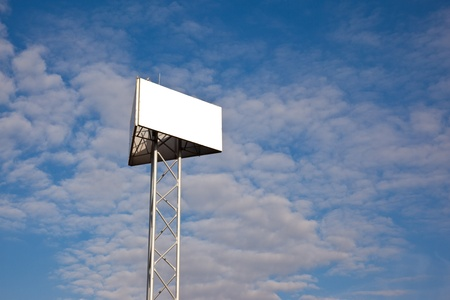 blank side of a triangular billboard against a blue sky  with clouds