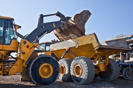 Wheel loader filling damp truck photo