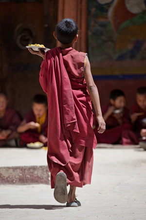 Young budhist monk bringing food photo