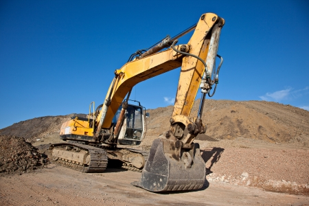 worksite: Excavator at a construction site with blue sky