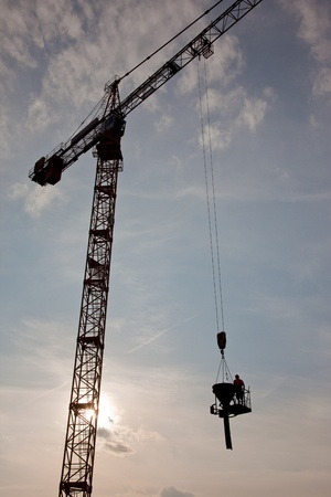 transported: Silhouette of construction worker being transported by jib crane with concrete Stock Photo