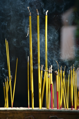 Smoking incence sticks at budhist pagoda photo