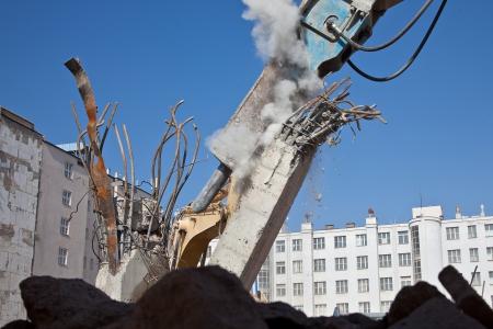 Hydraulic hammer demoliting concrete column photo