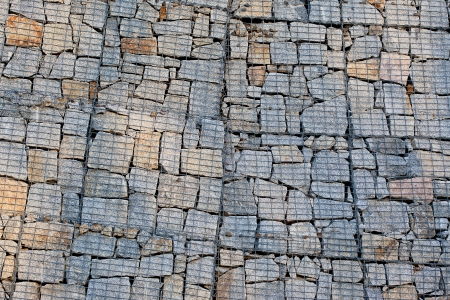 gabion: Gabion wall made of natural granite cubes