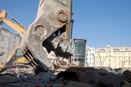 Jaw of hydraulic crusher at building demolition photo