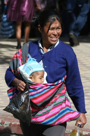 Bolivian woman carrying child in Cochabamba