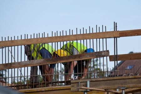 formwork: Workers preparing concrete bars