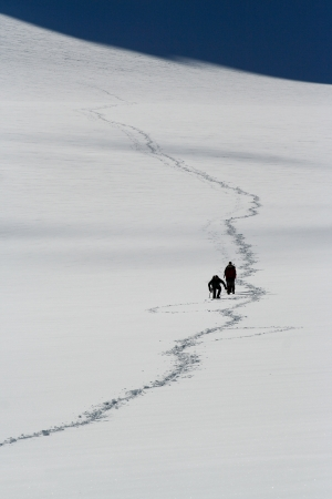 Path at snow field with climbers
