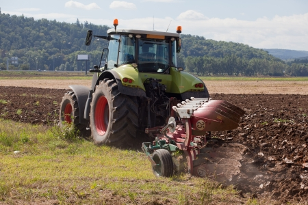 Ploughing soil with  farm tractor on the agriculture field Stock Photo