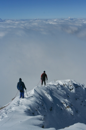 Climbers at snowy ridge above clouds Stock Photo
