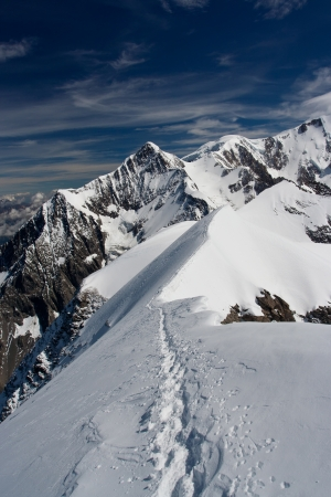 snow capped mountain: Climbers snow path along the ridge Stock Photo