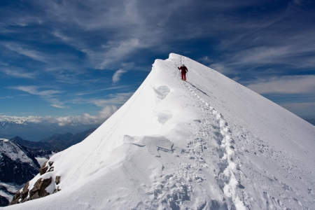Climber descending snowy peak at mountains