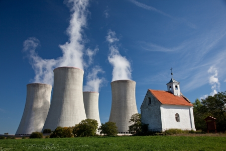 Cooling towers of nuclear powerplant with contrast of church