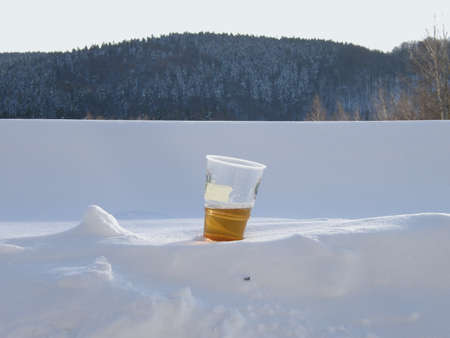 unspecified: cup of beer unspecified brand forgotten in the snow