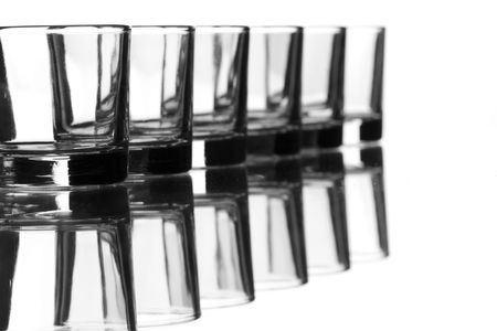 a row of small liqueur glasses reflected in a mirror