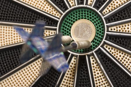 reveille: a dart thrown at a target where the center is a coin Stock Photo