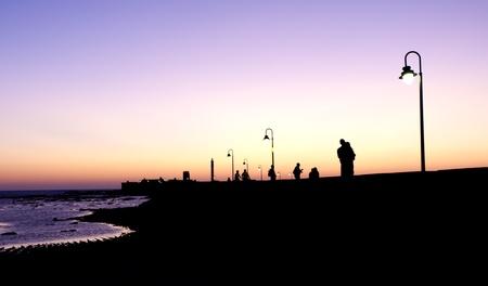 Varias parejas paseando por la noche por un paseo marítimo Foto de archivo - 10729213