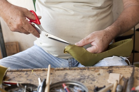a shoemaker by cutting the fabric of a shoe