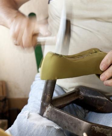 a shoemaker, striking the heel of a shoe lady
