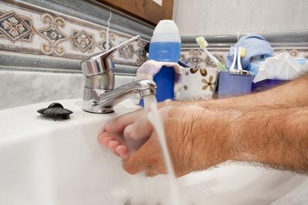 lavarse las manos: un hombre lavándose las manos en el lavabo Foto de archivo
