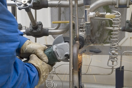 a worker cutting metal tubes Stock Photo