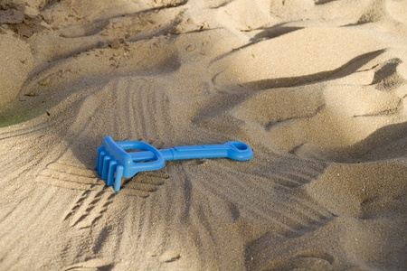 a rake in the sand on the beach to play with children Stock Photo