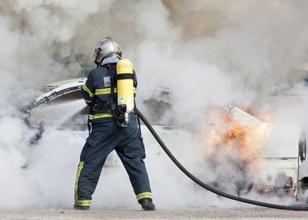 departamentos: un bombero apagando un coche que estaba ardiendo Foto de archivo