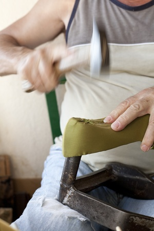 a shoemaker hammering some nails in a shoe