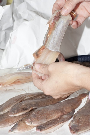 cleaning a fish in its sole fish shop for a customer
