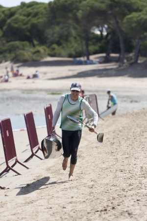 PUERTO REAL, SPAIN - JUNE 09: An unidentified canoeist arrives on shore during the veterans category in the championship canoe race Andalucia on June 09, 2012 in Puerto Real, Cadiz, Spain.