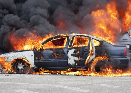 a burning car in the middle of the street