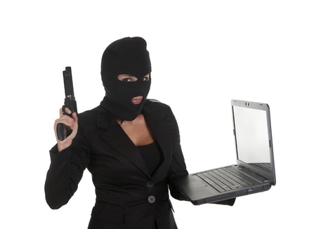 balaclava: a hacker, committing a crime  through laptop Stock Photo