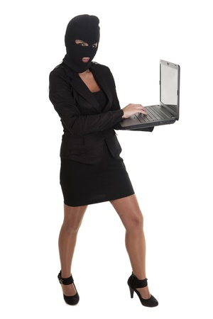 a hacker, committing a crime  through laptop Stock Photo