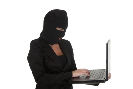 a hacker, committing a crime  through laptop Stock Photo - 16391845
