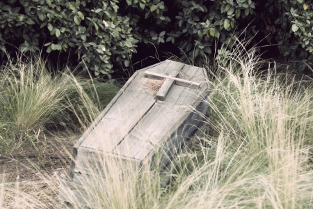 funeral background: an old wooden coffin with a cross on top