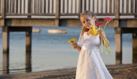 a girl in a wedding dress on the beach photo