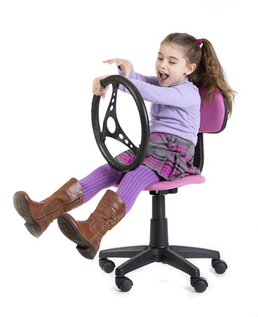 a young girl sitting with a steering wheel Stock Photo