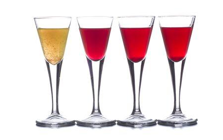 varios vasos de chupito con diferentes bebidas, que combinadas representan la bandera de un país Foto de archivo