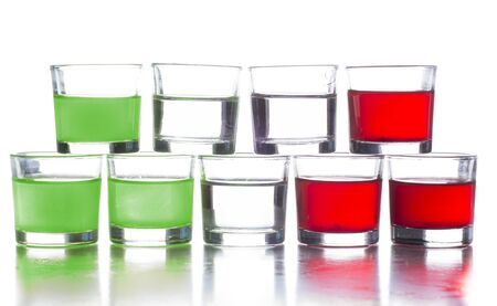 several shot glasses with different drinks, which combined represent the flag of a country Imagens