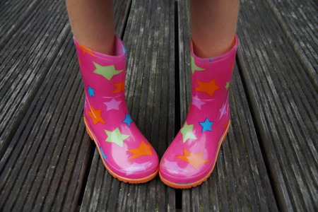 Cute kid legs in rubber boots on a rainy day