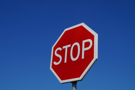 Stop Sign isolated on clean blue sky