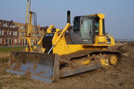 earth moving equipment: Almere, The Netherlands - March 19, 2015: Komatsu bulldozer sits at rest on a construction site