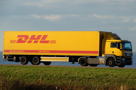 dyke: Almere Buiten, Flevoland, The Netherlands - November 17, 2014: DHL truck drives over a Dutch dike. DHL Express is a division of Deutsche Post providing international express mail services.