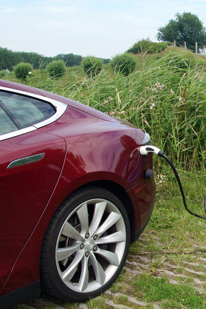 breaking new ground: Red Tesla Model S being charged - vertical