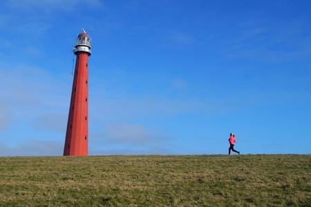 Woman running toward a Dutch red lighthouse