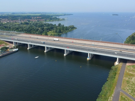 Aerial view of the highway A6 bridge ( Dutch Bridge ) connecting Dutch provinces of North Holland and Flevoland. In the back is a railroad bridge and the Markermeer.