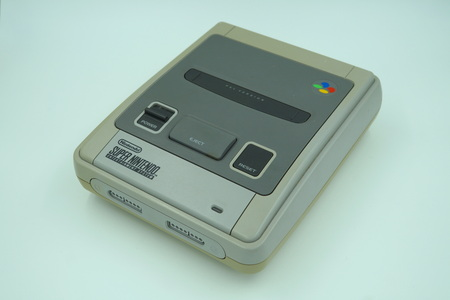 Classic Super Nintendo (SNES) video game console deck against a white background. Editorial