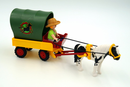 Playmobil coachman traveling by covered wagon, horse-drawn Western Wagon. Editoriali