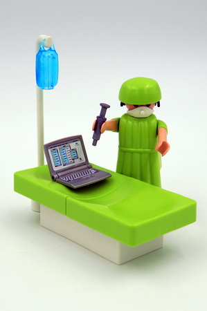 Playmobil doctor injecting antivirus in a vires infected computer.