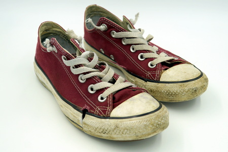 Dirty old torn vintage red canvas shoes - Converse All Stars